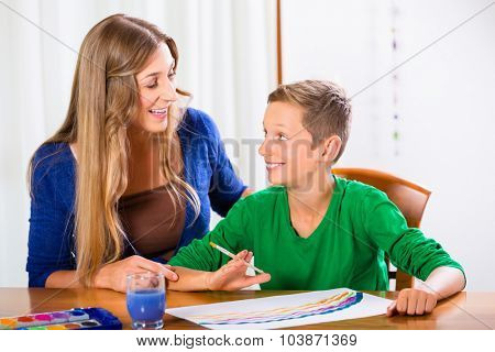 Mother and son painting picture with water color