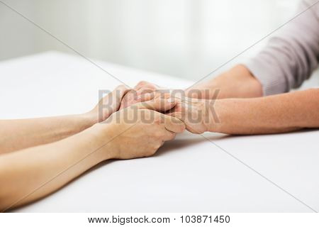 people, age, family, care and support concept - close up of senior woman and young woman holding hands