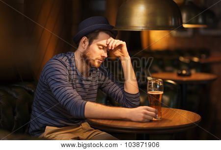 people, loneliness, alcohol and lifestyle concept - unhappy single young man in hat drinking beer at bar or pub