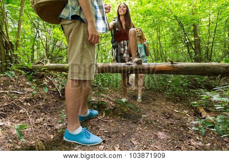 adventure, travel, tourism, hike and people concept - close up of friends walking with backpacks and climbing over fallen tree trunk in woods