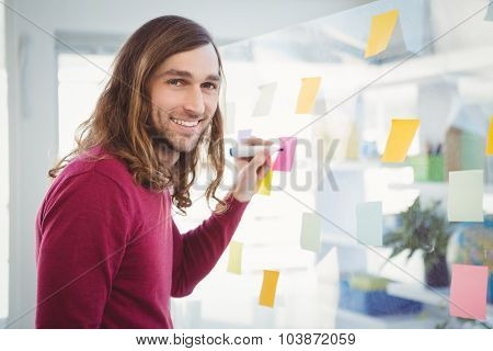 Portrait of hipster writing on sticky note stuck on glass in office
