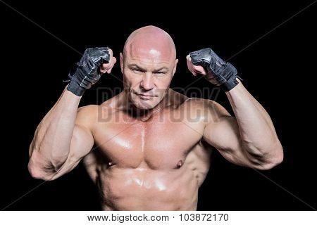 Portrait of bald man in gloves against black background