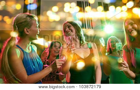 party, holidays, celebration, nightlife and people concept - happy young women with glasses of champagne in club
