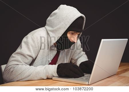 Hacker using laptop at desk in office