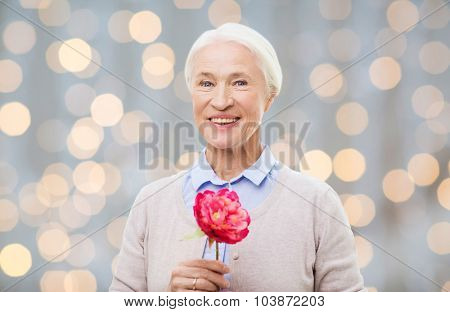 age, holidays and people concept - happy smiling senior woman with flower over holidays lights background