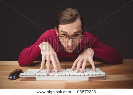 Portrait man wearing eye glasses typing on computer keyboard at desk in office