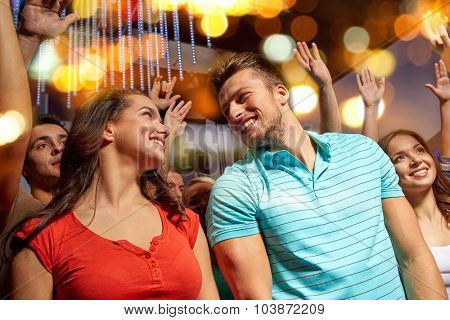 party, holidays, music, nightlife and people concept - happy couple having fun at concert in night club