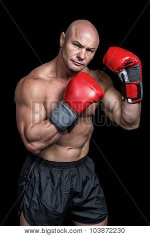 Portrait of boxer with red gloves against black background