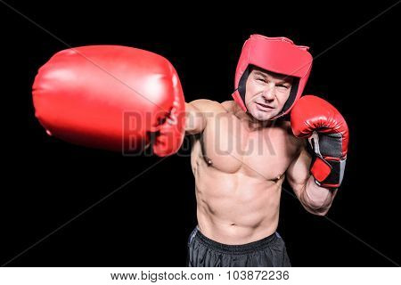 Boxer with red headgear punching against black background
