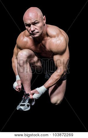 Portrait of muscular man tying laces against black background