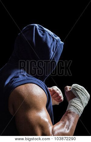 Muscular man in blue hood with fighting stance against black background