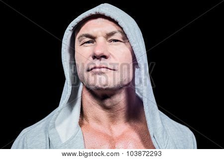 Portrait of confident man in grey hood against black background