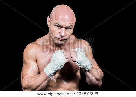 Portrait of confident man with fighting stance against black background