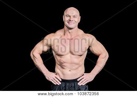 Portrait of smiling bald man with hand on hip standing against black background