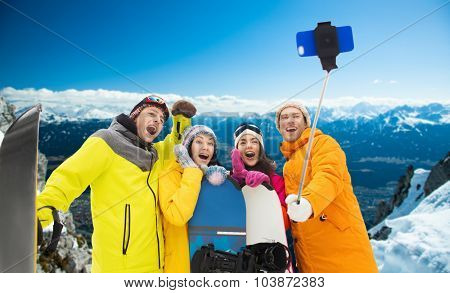 winter sport, leisure, friendship, technology and people concept - happy friends with snowboards and taking picture by smartphone on selfie stick over snowy mountains background