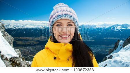 winter, leisure, clothing and people concept - happy young woman in winter clothes outdoors over snowy mountains background