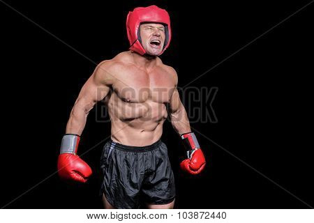 Angry boxer with gloves and headgear against black background