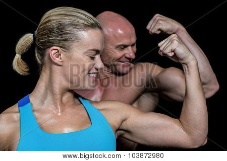Happy healthy man and woman flexing muscles against black background