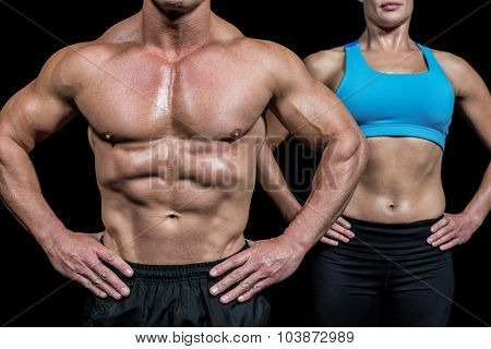 Midsection of man and woman with hands on hip against black background