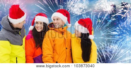 winter holidays, christmas, friendship and people concept - happy friends in santa hats and ski suits over firework background