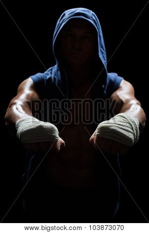 Athlete in hood with bandage on hand against black background