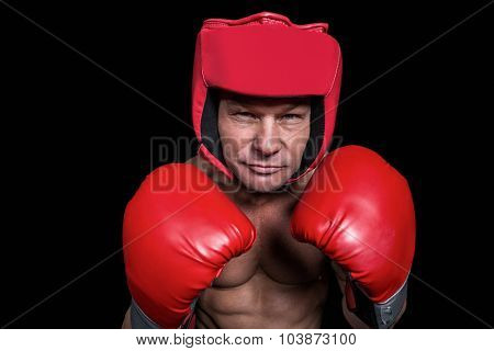 Portrait of boxer with gloves and headgear against black background