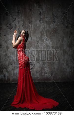 Beautiful girl in a red dress in studio