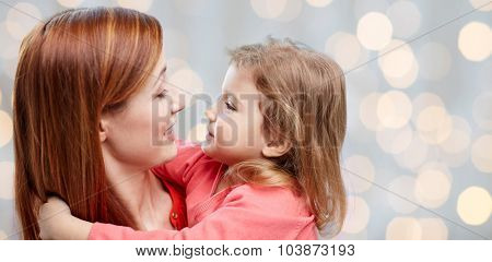 family, children and people concept - happy mother and little daughter hugging over holidays lights background
