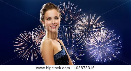 people, holidays and glamour concept - happy beautiful woman in evening dress over firework on dark blue background