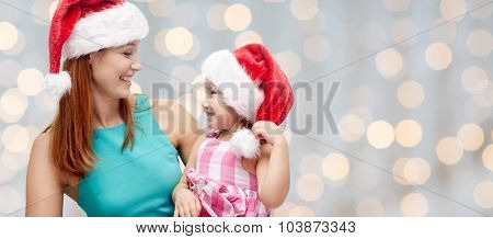 christmas, family, childhood and people concept - happy mother and little girl in santa hats over holidays lights background