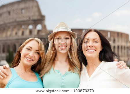 summer holidays, people, travel, tourism and vacation concept - group of smiling young women over coliseum in rome background
