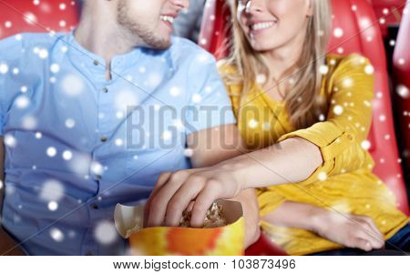entertainment, leisure and people concept - close up of happy couple watching movie and eating popcorn in theater or cinema over snowflakes