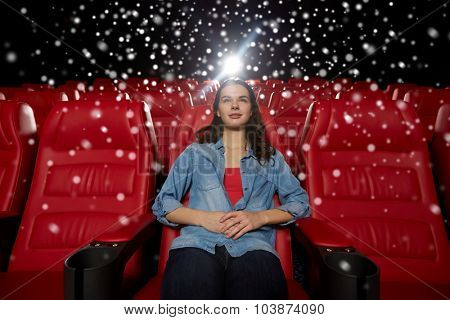cinema, entertainment and people concept - young woman watching movie alone in empty theater auditorium over snowflakes