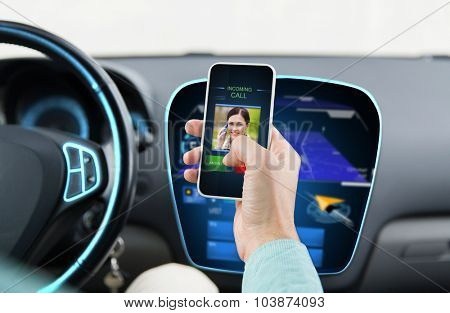 transport, business trip, communication, technology and people concept - close up of male hand with incoming video call icon on smartphone screen in car