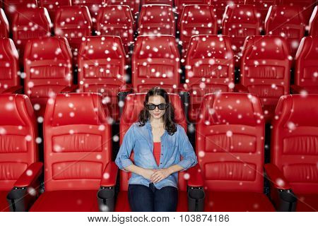 cinema, technology, entertainment and people concept - young woman with 3d glasses watching movie alone in empty theater auditorium over snowflakes