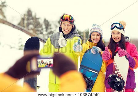 winter sport, technology, leisure, friendship and people concept - happy friends with snowboards and smartphone taking picture outdoors