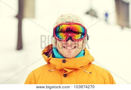 winter, leisure, sport and people concept - happy young man in ski goggles outdoors