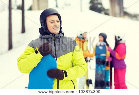 winter, leisure, extreme sport, friendship and people concept - happy young man in helmet with snowboard and group of friends