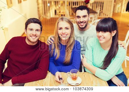 people, leisure, friendship and technology concept - group of happy friends with selfie stick taking picture and drinking tea at cafe