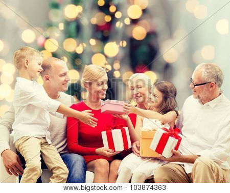 family, holidays, generation, christmas and people concept - smiling family with gift boxes sitting on couch over tree lights background