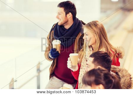 people, friendship, hot drinks and leisure concept - happy friends drinking from paper coffee cups on skating rink