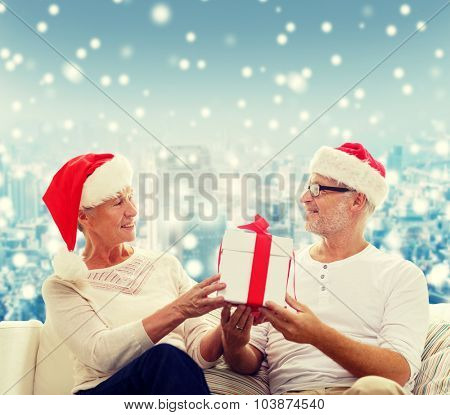 family, holidays, christmas, age and people concept - happy senior couple in santa helper hats with gift box over snowy city background