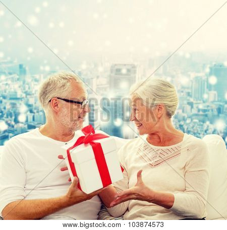 family, holidays, christmas, age and people concept - happy senior couple with gift box over snowy city background