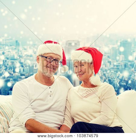 family, holidays, christmas, age and people concept - happy senior couple in santa helper hats sitting on sofa over snowy city background