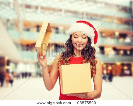 christmas, holidays, celebration and people concept - smiling woman in santa helper hat with gift box over shopping center background