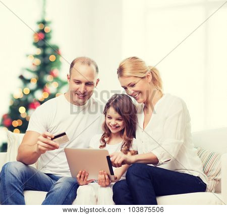 family, holidays, technology and people - smiling mother, father and little girl with tablet pc computers over living room and christmas tree background