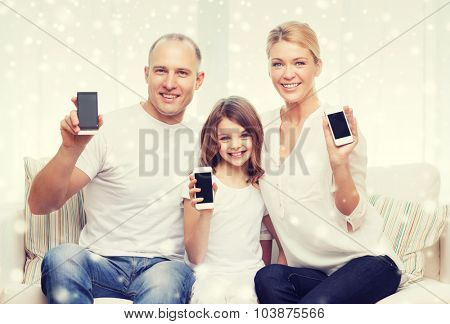 holidays, technology, advertisement and people concept - smiling family showing smartphones blank screens over snowflakes background