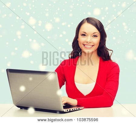 christmas, x-mas, electronics, gadget concept - smiling woman in red clothes with laptop computer