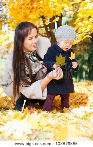 Young happy mother with daughter in autumn park