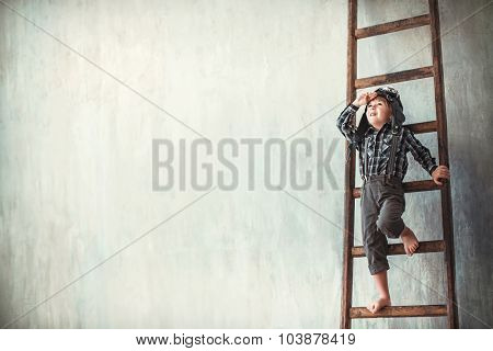Little boy in a helmet on the ladder
